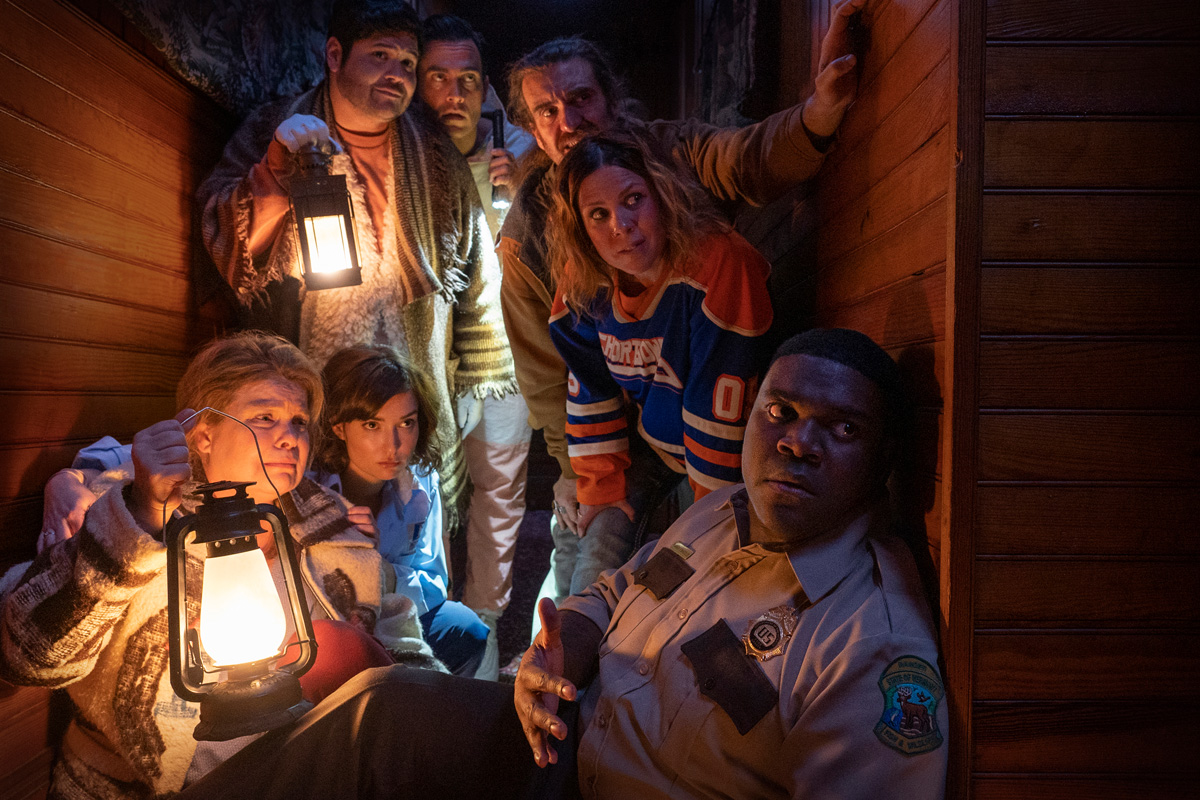 (Clockwise from lower right) Sam Richardson, Milana Vayntrub, Catherine Curtin, Harvey Guillen, Cheyenne Jackson, George Basil and Sarah Burns in WEREWOLVES WITHIN, produced by Ubisoft Film & Television, Vanishing Angle, and Sam Richardson. IFC Films will release the film June 25th, 2021 in select theaters and on demand.